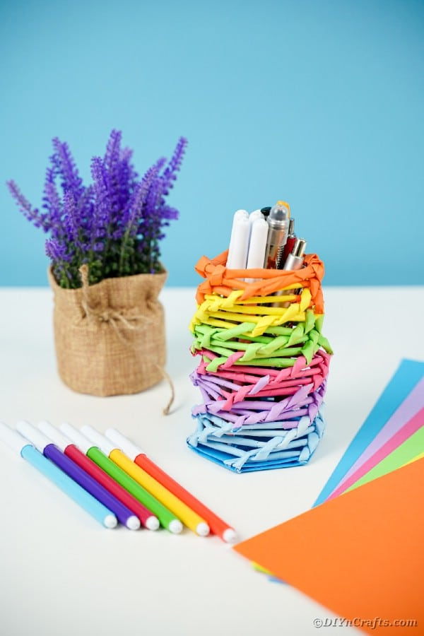 Straw Rainbow Organizer can next to a lavender plant.