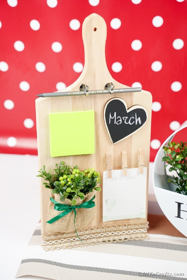 Cutting board by flower decor in front of red and white background