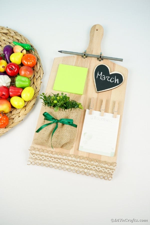 Cutting board memo station next to plastic fruit on woven mat