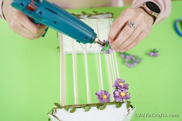 Gluing flowers onto birdcage