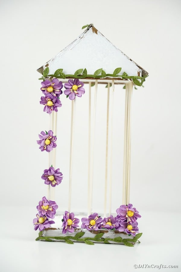 White birdcage with purple flowers on white surface