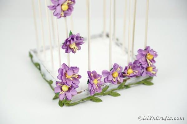 Bottom of DIY birdcage with purple flowers