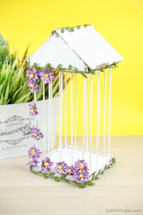 Birdcage by flower pot with yellow background