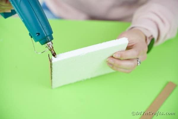 Gluing cardboard strips on styrofoam base