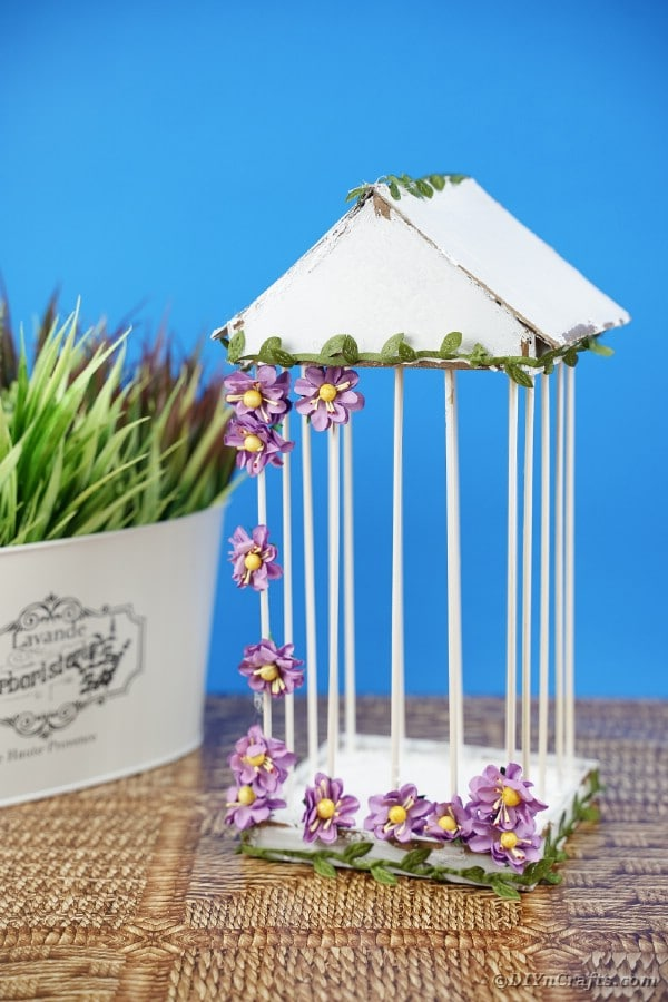 Birdcage by flower pot with blue background