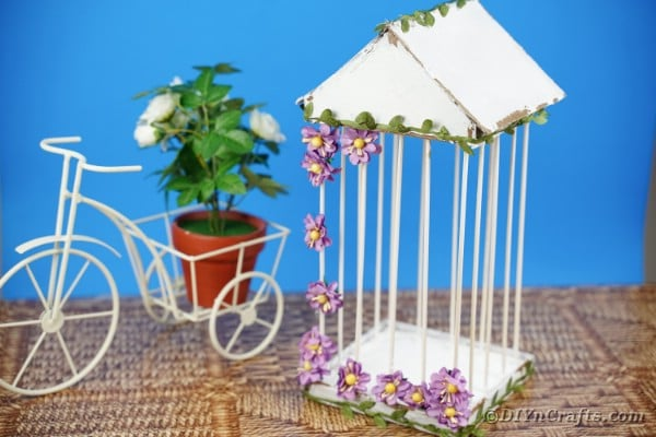 Birdcage by wire bicycle with blue background