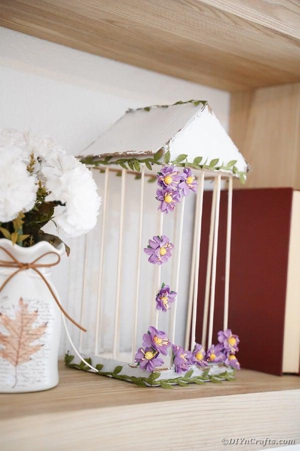 White birdcage with purple flowers on bookshelf