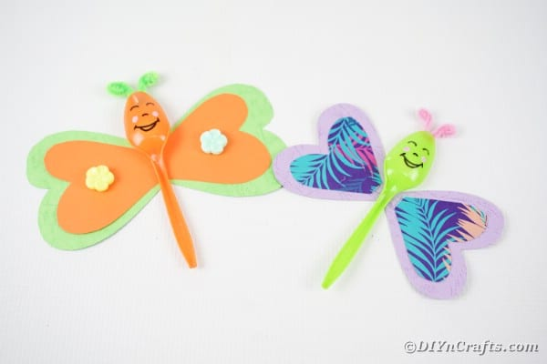 Green and orange butterfly spoons on white table