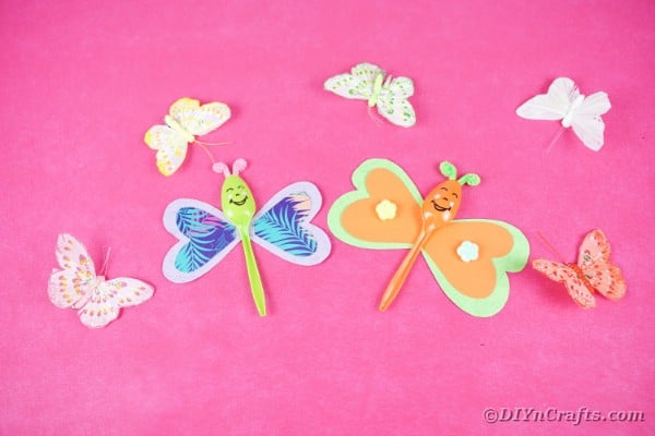 Butterfly spoons on pink paper