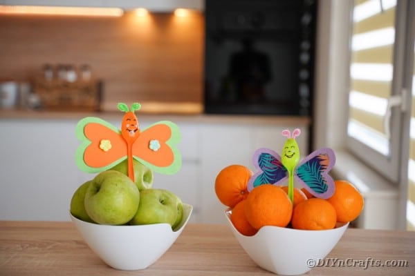 Butterfly spoons in bowls of fruit