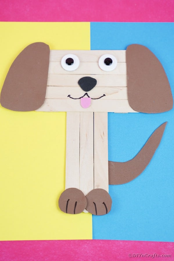 Craft stick puppy on blue and yellow paper