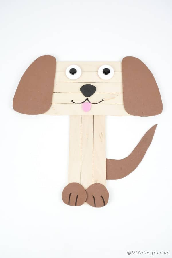 Craft stick puppy on white surface