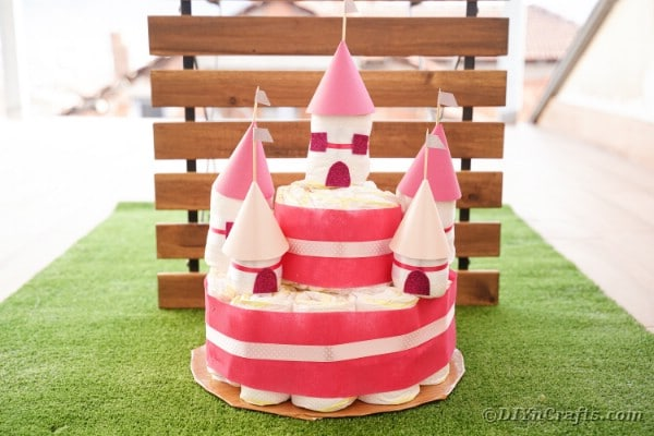 "Gâteau de château de couches devant des lattes de bois ""width ="" 600 ""height ="" 400 ""srcset ="" https://cdn.diyncrafts.com/wp-content/uploads/2020/05/Diaper-Castle-27.jpg 600w , https://cdn.diyncrafts.com/wp-content/uploads/2020/05/Diaper-Castle-27-300x200.jpg 300w ""tailles ="" (largeur max: 600px) 100vw, 600px"