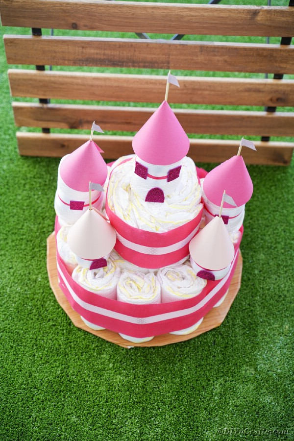 Diaper castle cake in front of wooden slats