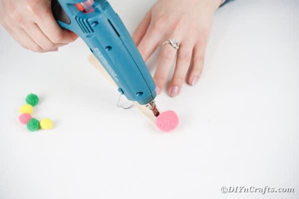 Gluing pom pom to craft stick