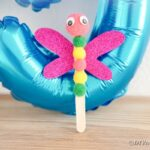 Dragonflly in front of blue balloon