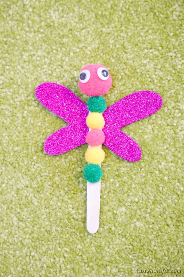 Craft stick dragonfly laying on grass