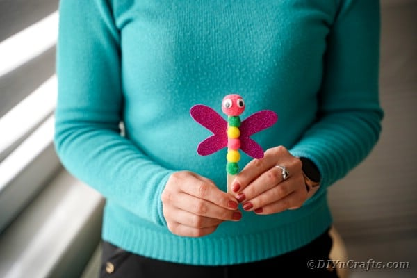 Women in teal shirt holding dragonfly craft