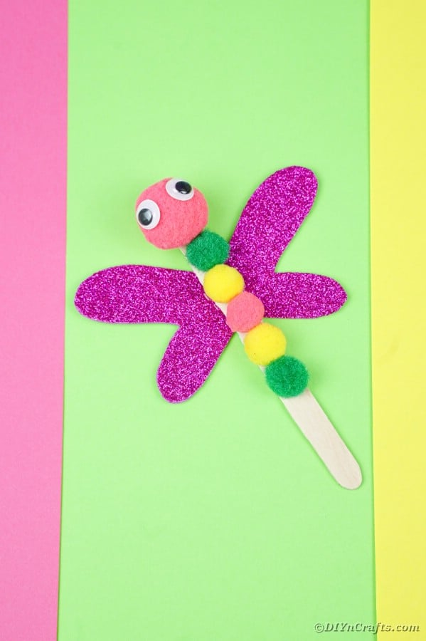 Craft stick dragonfly on green paper