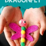 Craft stick dragonfly in woman's hands