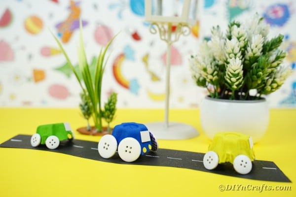 Toy egg carton cars in front of colorful background