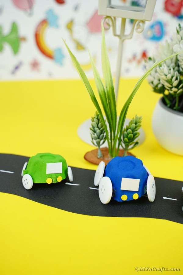 Green and blue toy cars on yellow surface