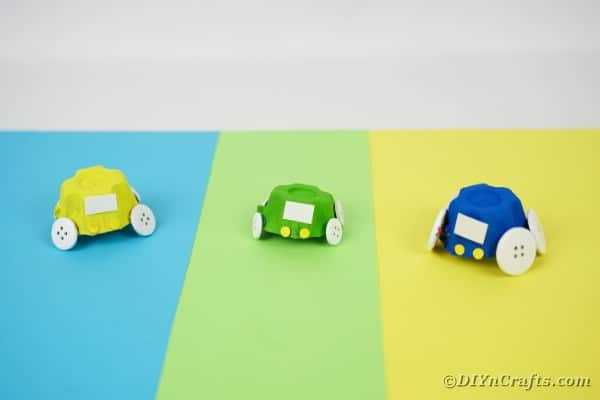 Three egg carton cars on colored paper