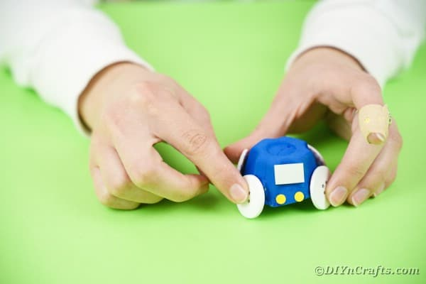 Gluing button wheels onto blue toy car