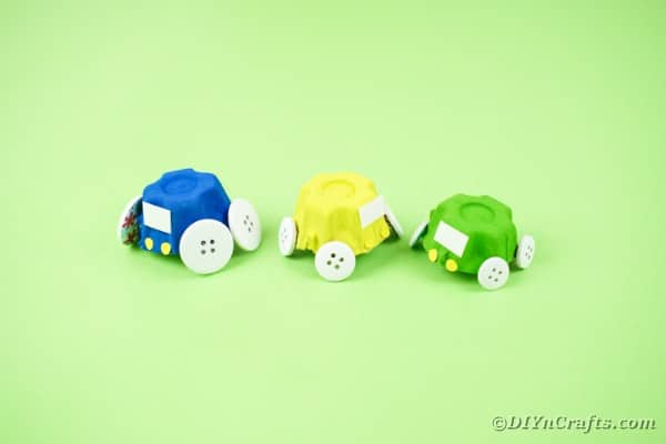 Blue yellow and green toy cars on green paper