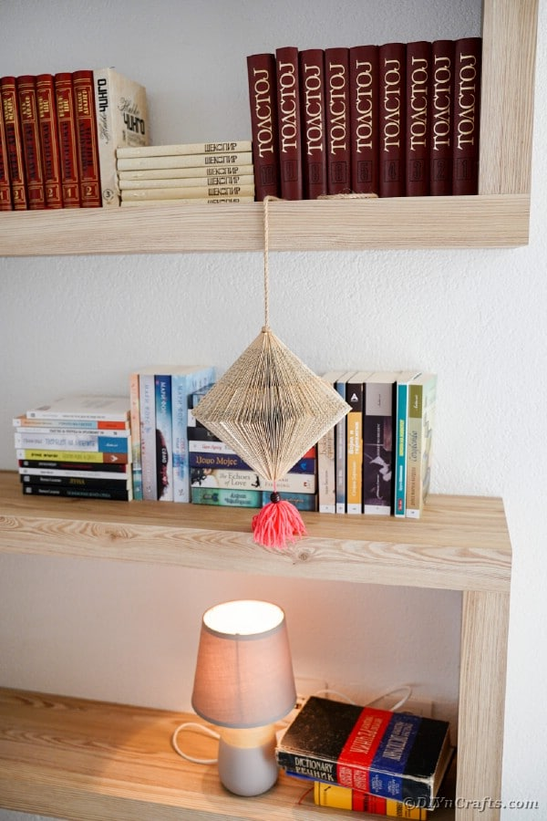 Book page lantern hanging in front of bookshelf