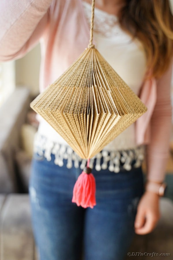 Woman holding paper lantern with pink tassel
