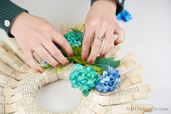 Placing blue flowers on wreath