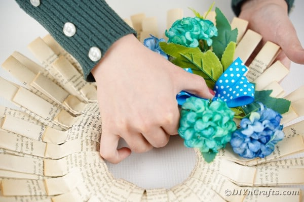Adding blue polka dot bow to flowers on paper wreath