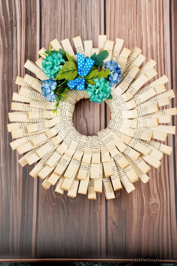 Old book page wreath on wooden wall