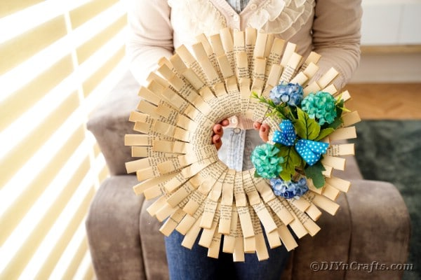 Woman holding folded paper wreath