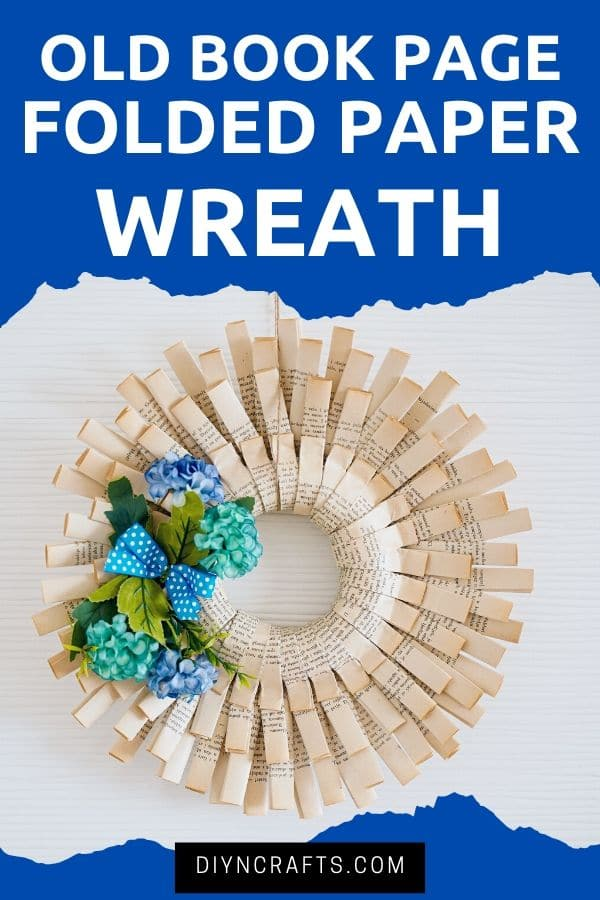 Paper wreath with blue flowers on white wall