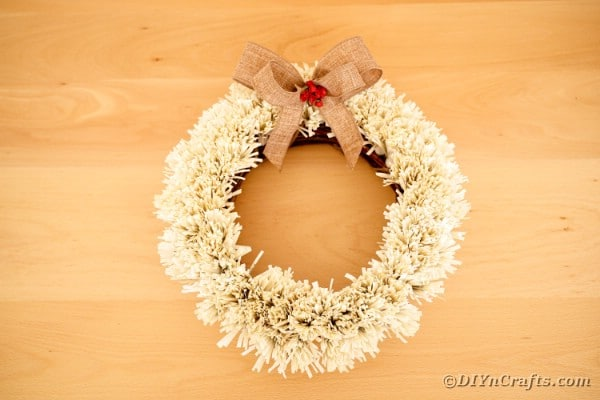 Old book page wreath against blonde wood background