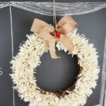Fringed wreath hanging on chalkboard