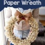 Woman holding paper fringe wreath