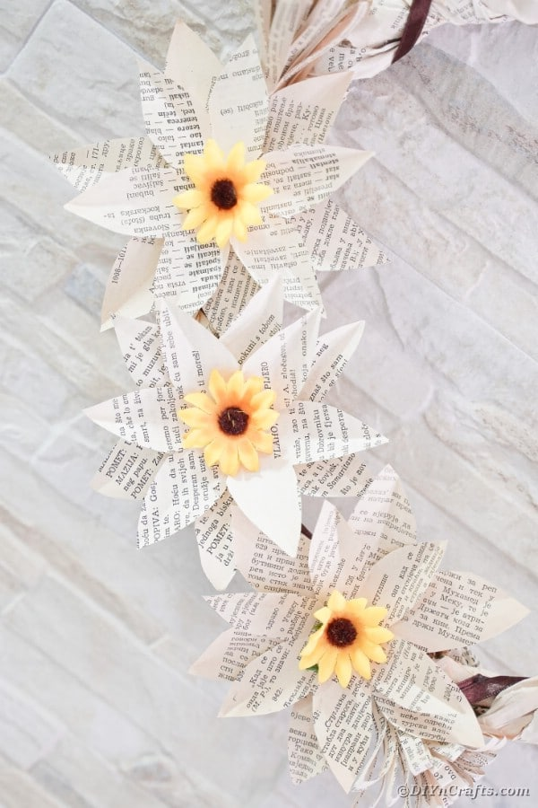 Book page sunflowers on brick wall