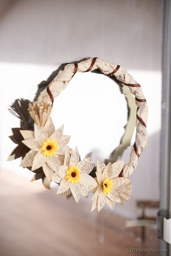 Book page grapevine wreath hanging on window