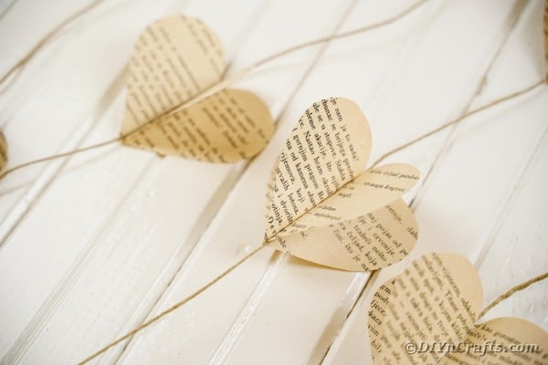 Old book page paper heart garland on white wood