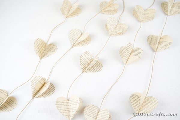Old book page paper heart garland on white background