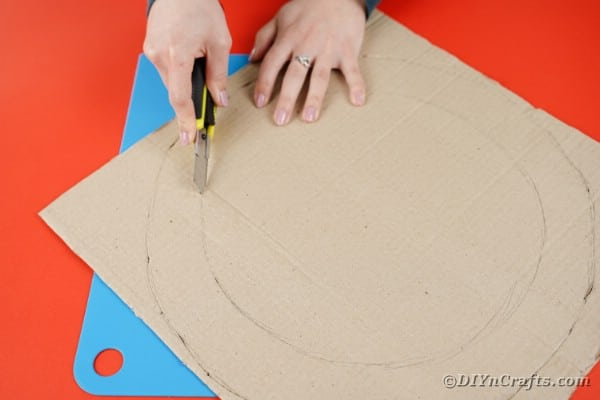 Woman cutting circle out of cardboard