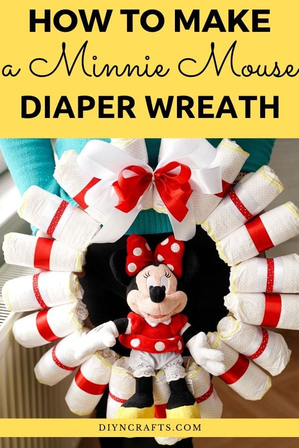 Women in blue holding diaper wreath