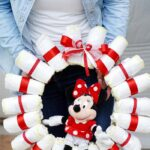 Women in blue and white holding diaper wreath
