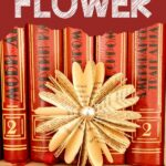 Paper flower in front of stack of books