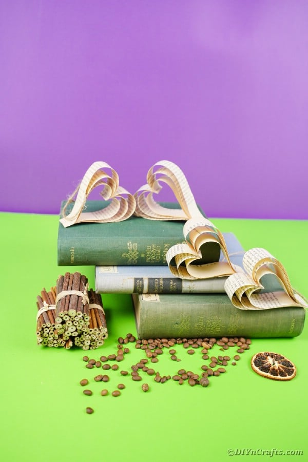 Paper hearts on stacked books on green table
