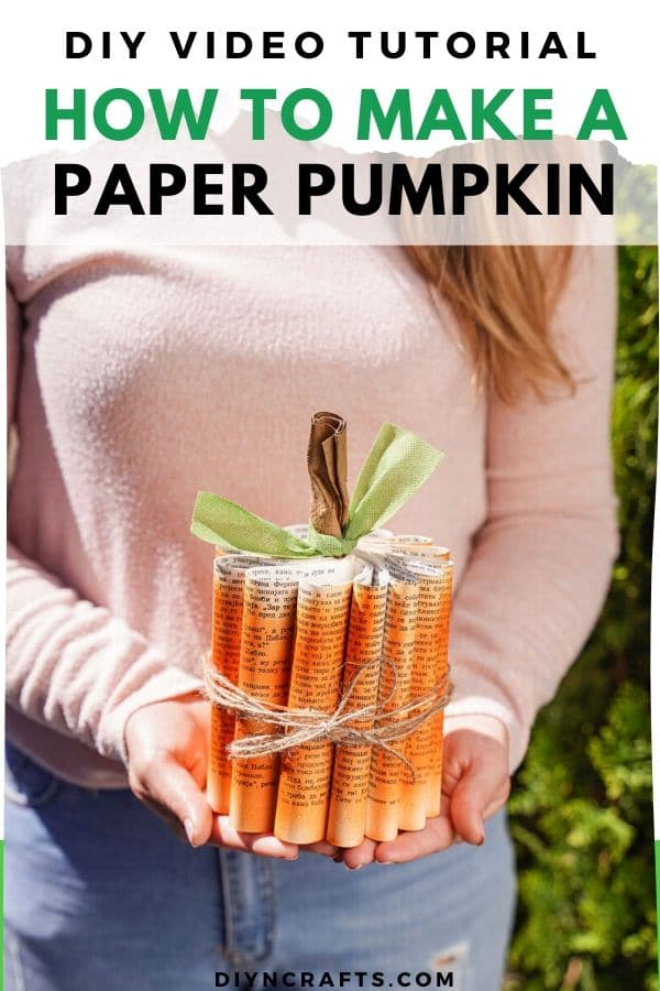 Woman in pink sweater holding paper pumpkin