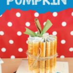 Book page pumpkin on stack of books by polka dot background